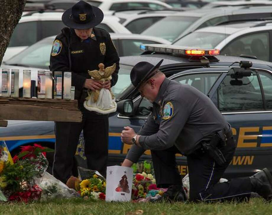 Newtown Police officers light a candle at a makeshift memorial outside of Saint Rose Lima Church in Newtown. Several prayer services were held today in memory of the Sandy Hook Elementary School Shootings. Photo by Mia M. Malafronte