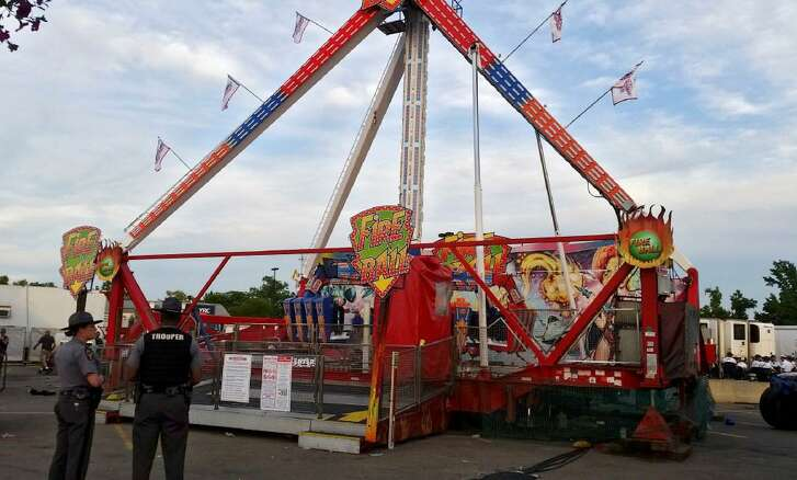 Authorities stand near the Fire Ball amusement ride after the ride malfunctioned, killing one and injuring several at the Ohio State Fair, Wednesday, July 26, 2017, in Columbus, Ohio.