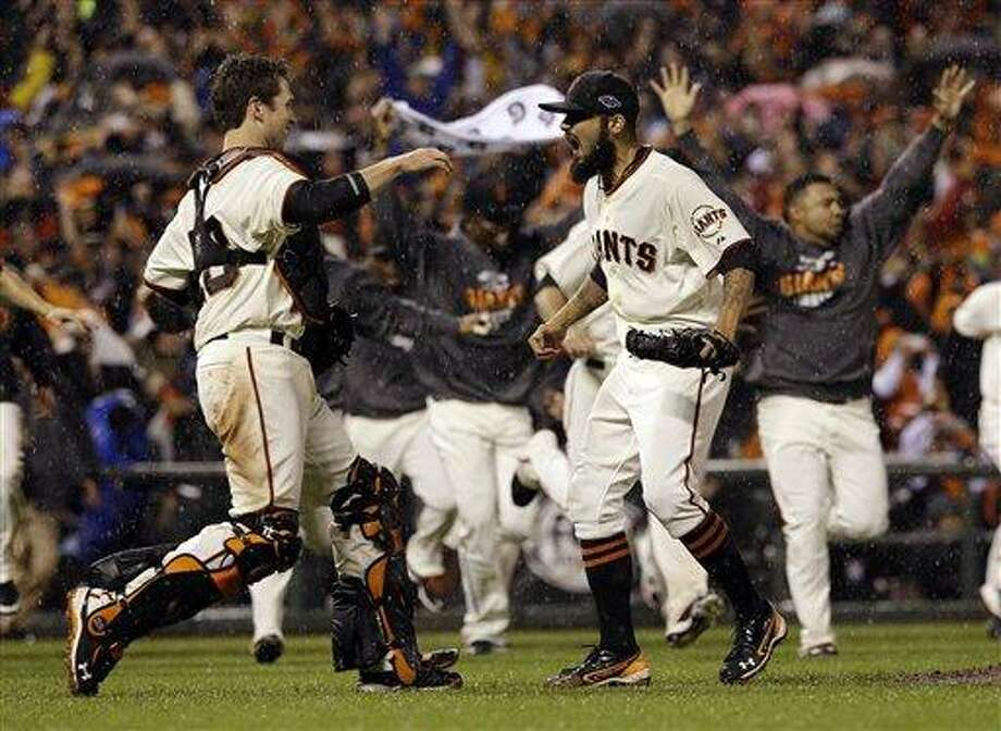 San Francisco Giants relief pitcher Sergio Romo and catcher Buster Posey react after the final out in Game 7 of baseball's National League championship series against the St. Louis Cardinals Monday, Oct. 22, 2012, in San Francisco. The Giants won 9-0 to win the series. (AP Photo/David J. Phillip) Photo: AP / AP