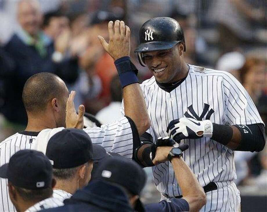New York Yankees' Robinson Cano, right, returns to the dugout after a solo home run off Cleveland Indians starting pitcher Josh Tomlin during a baseball game at Yankee Stadium in New York, Monday, June 25, 2012. It was Cano's second home run of the game. (AP Photo/Kathy Willens) Photo: AP / AP