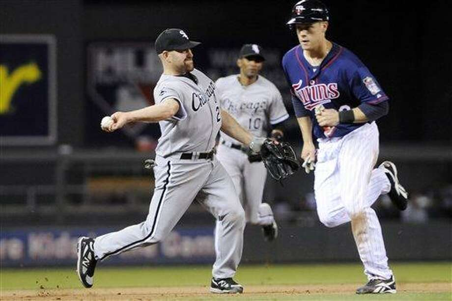 Minnesota Twins' Justin Morneau, right, runs by as Chicago White Sox third baseman Kevin Youkilis, left, throws out Twins' Drew Butera to end the eighth inning with the bases loaded in a baseball game, Monday, June 25, 2012, in Minneapolis. The Twins won 4-1. (AP Photo/Jim Mone) Photo: AP / AP