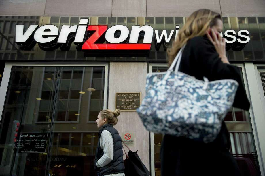 A pedestrian talks on a mobile phone as she walks past a Verizon Wireless retail store in Washington, D.C. On Thursday, Verizon's shares rose as much as 4.5 percent to $46.41, the biggest intraday gain since July 2009. Photo: Bloomberg News File Photo / © 2014 Bloomberg Finance LP