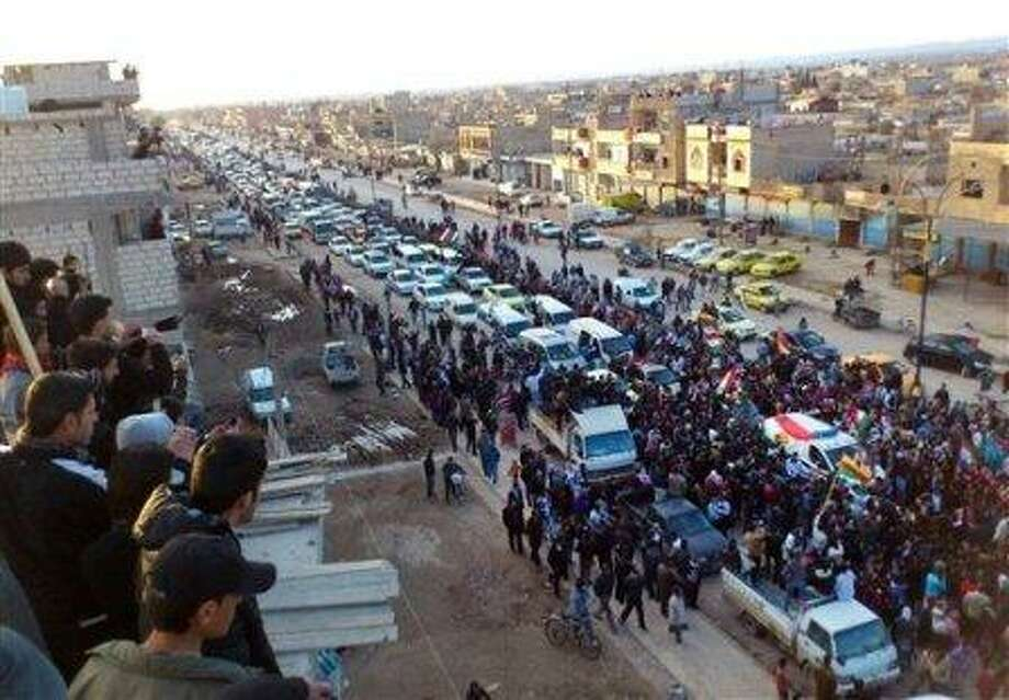 In this Wednesday, Feb. 22, 2012 citizen journalism image provided by the Local Coordination Committees in Syria and accessed on Thursday, Feb. 23, 2012, anti-Syrian regime protesters hold up Kurdish flags with a fleet of cars during a rally in the northeastern town of Qamishli, Syria. (AP Photo/Local Coordination Committees in Syria) THE ASSOCIATED PRESS IS UNABLE TO INDEPENDENTLY VERIFY THE AUTHENTICITY, CONTENT, LOCATION OR DATE OF THIS HANDOUT PHOTO
