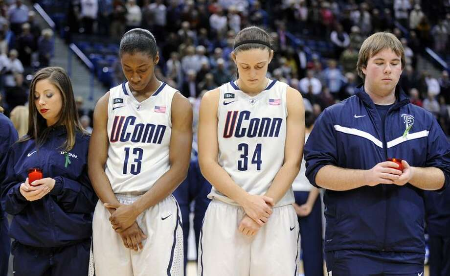 Members of the Connecticut's band, cheer, dance and basketball teams participate with members of the women's basketball team in a service in memory of those killed in Friday's school shooting in Newtown, Conn., before an NCAA college basketball game against Oakland in Hartford, Conn., Wednesday, Dec. 19, 2012. (AP Photo/Fred Beckham) Photo: AP / FR153656 AP