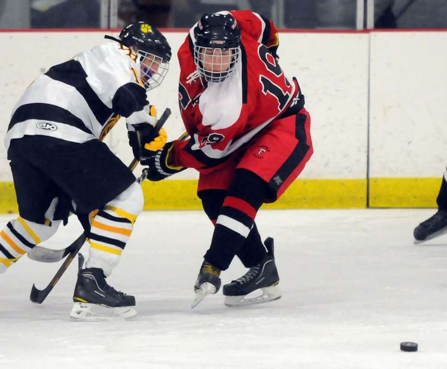 Hand's Danny Braumann, left, and Fairfield Warde/Ludlowe's Paul Barlow are about to head toward the puck during Hand's 3-1 win. Mara Lavitt/New Haven Register.