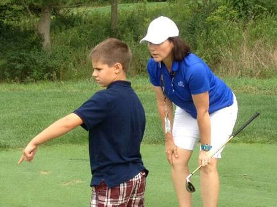 Submitted PhotoTurning Stone Assistant Golf Professional Michelle Murphy helps Matt Rushford, 8, size up his putt at Sandstone Hollow Golf Course as part of The First Tee of Syracuse program.