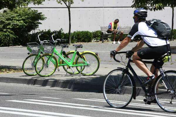 LimeBike, one of two new dock-less bike share programs, has placed bikes for public use around the city, including these two in lower Queen Anne, July 26, 2017. Bikes are unlocked via an app and do not come with helmets.