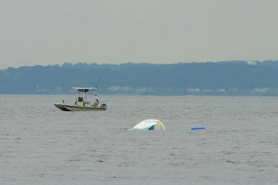 Four men were rescued off a small fishing boat, which is still in the water flipped upside down, at the end of Shippan Point on Wednesday night. Photographed in Stamford, Conn. on Thursday, July 27, 2017. Photo: Michael Cummo / Hearst Connecticut Media / Stamford Advocate