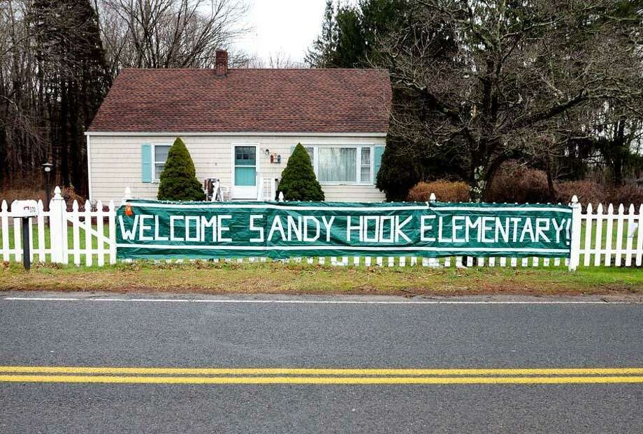 "A ""Welcome Sandy Hook Elementary!"" sign is posted Tuesday at a home on Fan Hill Road in Monroe across from the entrance to the school being readied for the students. The Sandy Hook Elementary School students whose classmates and teachers were killed in Friday's shooting will not be in school Wednesday as was previously planned. Photo by Arnold Gold/New Haven Register"
