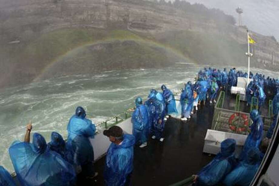 AP PhotoMaid of the Mist's Senior Capt. Malcolm Bunting, not shown, pilots tourist in front of a rainbow on the Maid of the Mist tour boat in Niagara Falls, Ontario in August. Photo: AP / AP2011