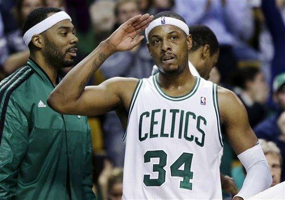 Boston Celtics forward Paul Pierce (34) acknowledges the crowd as he leaves the court late in the fourth quarter of an NBA basketball game against the Cleveland Cavaliers in Boston, Wednesday, Dec. 19, 2012. Pierce scored 40 points to lead the Celtics to a 103-91 victory. Celtics forward Chris Wilcox watches at left. (AP Photo/Elise Amendola) Photo: ASSOCIATED PRESS / AP2012