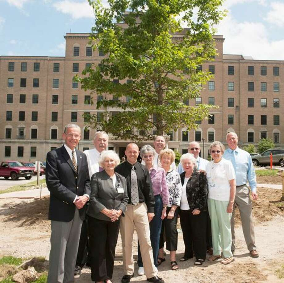Board, Auxiliary and staff members of the Charlotte Hungerford Hospital's Front Circle Beautification Committee gather to welcome a new 20-foot white oak tree planted to replace  the century old tree lost in last year's October snowstorm. / ALAN GRANT