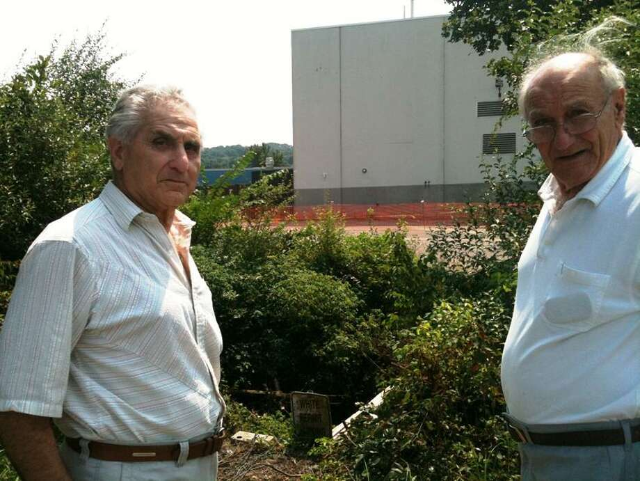 Vincent and Anthony DePaola on their land that borders Covidien in North Haven.  Ann DeMatteo/Register