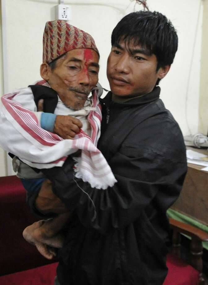 A relative carries Nepalese Chandra Bahadur Dangi, 72, who claims to be only 22 inches tall, in Nepalgunj, Nepal, Tuesday. Dangi is hoping to prove to Guinness World Records that he's the world's shortest man. Guinness World Records currently recognizes Junrey Balawing of the Philippines, who is 23.5 inches tall, as the shortest man in the world. (AP Photo/Subrot Neupane) Photo: ASSOCIATED PRESS / AP2011