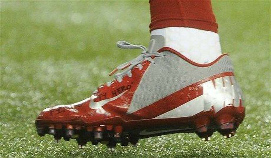 in this Sunday, Dec. 16, 2012, photo, a shoe worn by New York Giants wide receiver Victor Cruz bears a message dedicated to 6-year-old Jack Pinto, one of the victims in last week's school shootings at Sandy Hook Elementary School in Newtown, Conn., as Cruz warms up for the Giants' NFL football game against the Atlanta Falcons in Atlanta. (AP Photo/John Amis) Photo: AP / FR69715 AP