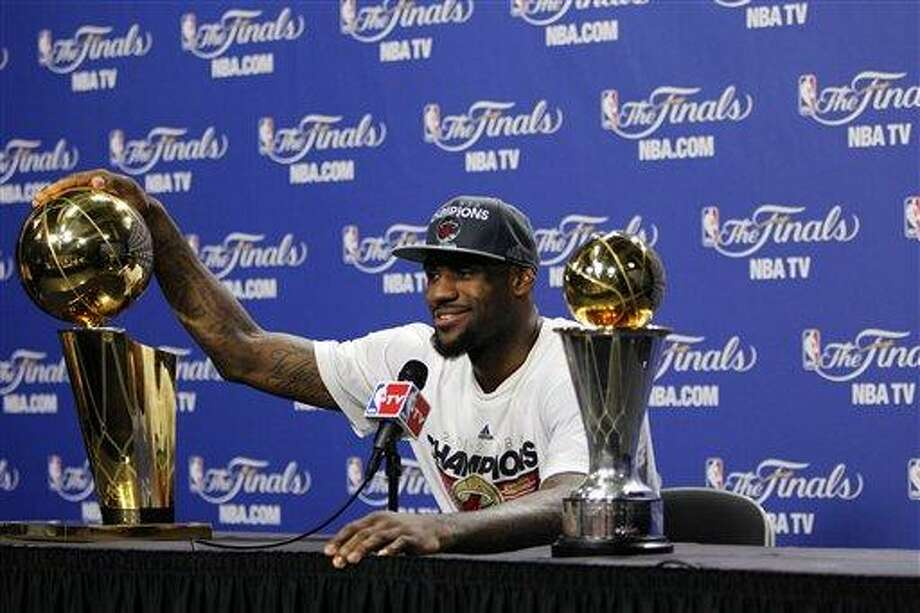 Miami Heat small forward LeBron James rests his hand on the Larry O'Brien NBA Championship Trophy during a news conference after Game 5 of the NBA finals basketball series against the Oklahoma City Thunder, Friday, June 22, 2012, in Miami. The Heat won 121-106 to become the 2012 NBA Champions. His most valuable player trophy is at right. (AP Photo/Lynne Sladky) Photo: ASSOCIATED PRESS / AP2012