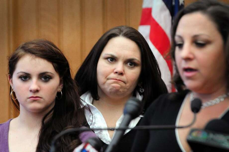 Dawn Duddy, right, sister of Branford murder victim Kathy Hardy, speaks at a Capitol press conference. Looking on are her sister, Jennifer Paul, center, and daughter, Maggie Duddy. They fear that budget cuts will end the state's cold case investigations.    Melanie Stengel/Register