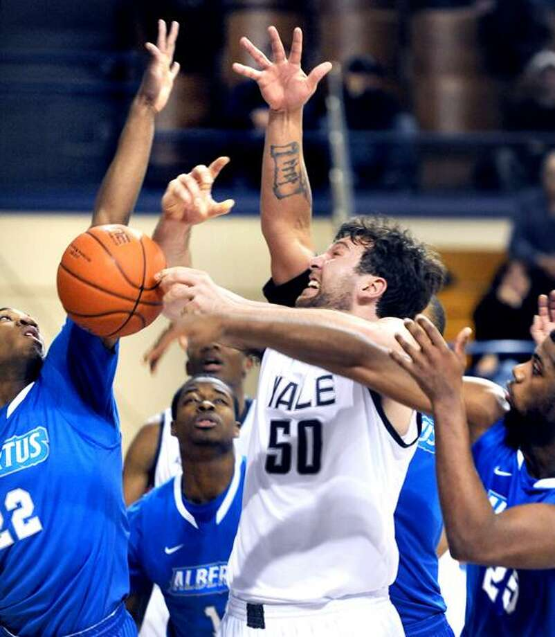 Jeremiah Kreisberg (center) of Yale loses the ball between Julian Sanders (left) and Darius Watson (right) of Albertus Magnus in the first half on 12/18/2012.Photo by Arnold Gold/New Haven Register
