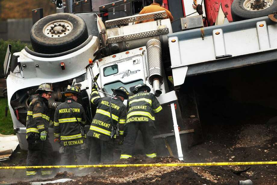 Catherine Avalone/The Middletown Press Middletown firefighters are at the scene of a fatal crash on Washington Street in Middletown involving a dump truck and four door sedan.