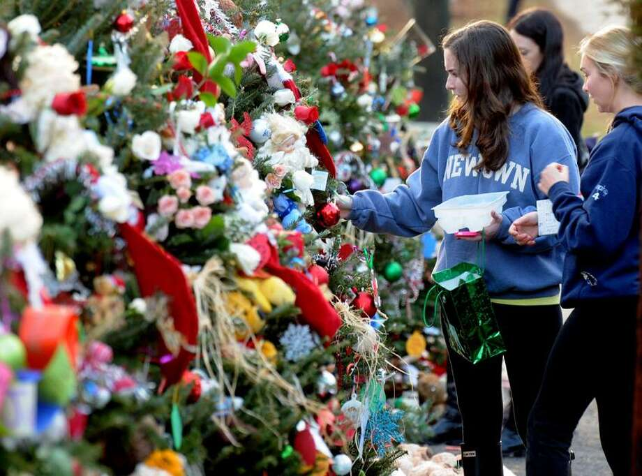 Lauralton Hall students Julie LePerch left and Helene Sorensen, both of Newtown, hung ornaments donated or made by the students of Lauralton Hall, at the Christmas trees erected at the makeshift memorial at the entrance to the Sandy Hook School. Since the girls live in town they volunteered to hang the ornaments for their classmates. Mara Lavitt/New Haven Register