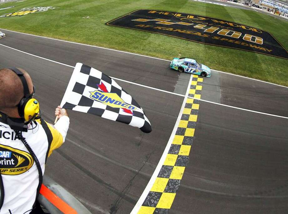 Matt Kenseth (17) takes the checkered flag to win the NASCAR Sprint Cup Series auto race at Kansas Speedway in Kansas City, Kan., Sunday, Oct. 21, 2012. (AP Photo/Tyler Barrick, Pool) Photo: AP / AP2012