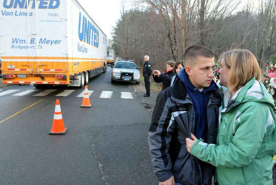Sandy Hook, Newtown: Sean and Jessica McGuire of Sandy Hook, Newtown, watch as moving vans return to Sandy Hook School to pick up more items to move to a school in Monroe.  The two visited the makeshift memorial at the entrance to the Sandy Hook School and prayed the rosary. Mara Lavitt/New Haven Register12/18/12
