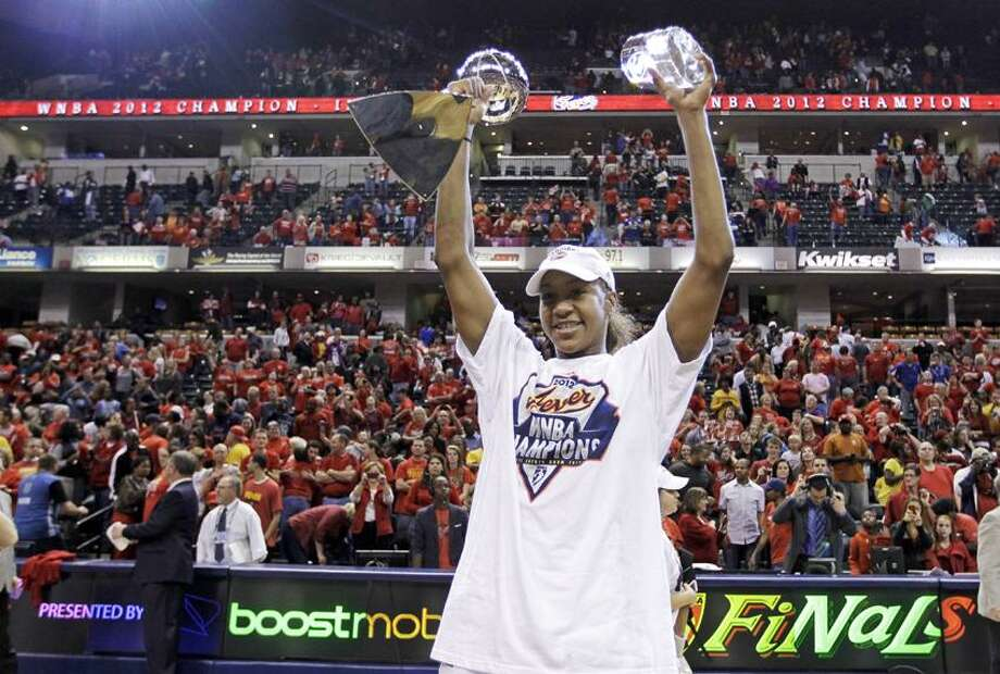 Indiana Fever forward Tamika Catchings celebrates with the trophy and the MVP award after winning the WNBA basketball Finals against the Minnesota Lynx in Indianapolis, Sunday, Oct. 21, 2012. The Fever won 87-78 to clinch their first WNBA championship. (AP Photo/Michael Conroy) Photo: AP / AP