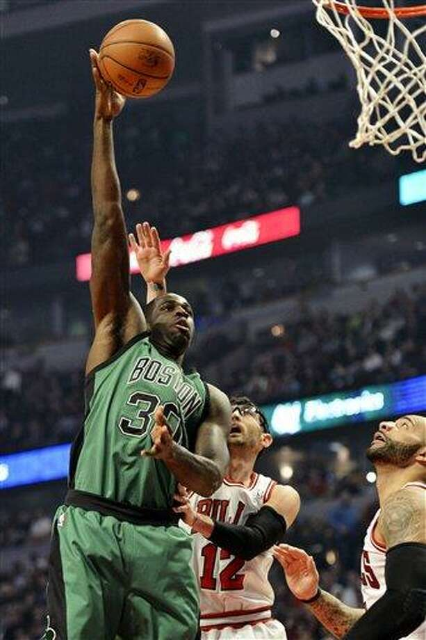 Boston Celtics forward Brandon Bass, left, shoots as Chicago Bulls guard Kirk Hinrich (12) and forward Carlos Boozer defend during the first quarter of an NBA basketball game, Tuesday, Dec. 18, 2012, in Chicago. (AP Photo/Brian Kersey) Photo: ASSOCIATED PRESS / AP2012