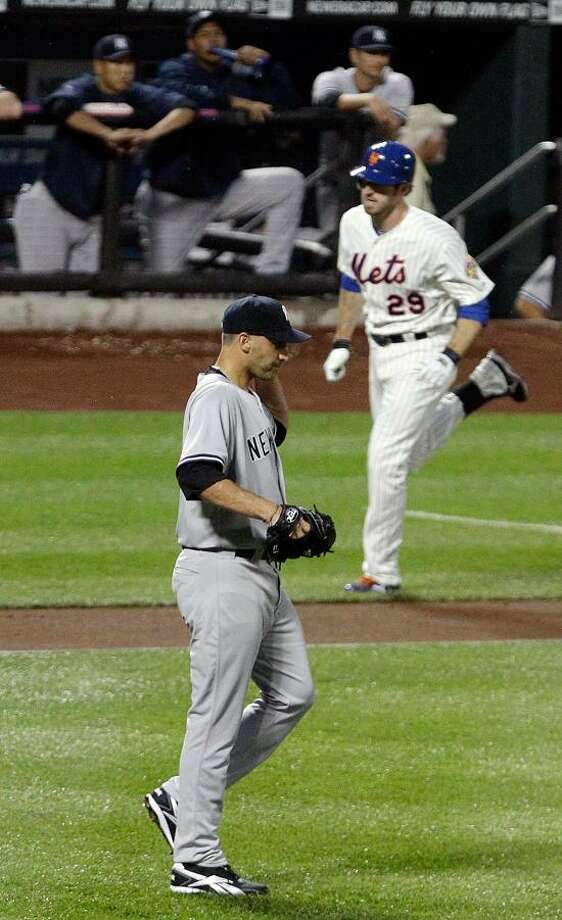 New York Yankees starting pitcher Andy Pettitte, bottom, looks on as New York Mets' Ike Davis (29) heads to home plate after hitting a three-run home run during the first inning of an interleague baseball game on Friday, June 22, 2012, in New York. (AP Photo/Frank Franklin II) Photo: AP / AP2012