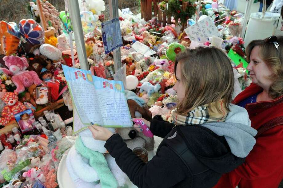Kristin Hawley left and her mother Tiina both of Danbury look over a collection of letters to the families and heroes of the Sandy Hook School shooting, at the makeshift memorial at the entrance to the Sandy Hook School. Mara Lavitt/New Haven Register