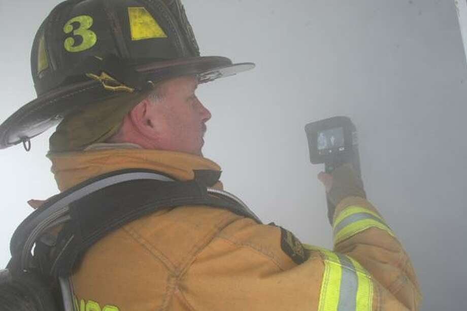 "Dispatch Staff Photo by JOHN HAEGER <a href=""http://twitter.com/oneidaphoto"">twitter.com/oneidaphoto</a> A firefighter show how a themoral imaging camera is used to search during a fire during traing in Chittenango  on Sunday, Oct. 21 2012."