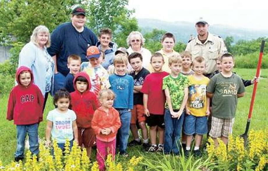 "Submitted Photo The Munnsville Pack 7 Cub Scouts stand with a recently planted a memorial Girard's scarlet azalea shrub at the American Legion Post 54 honoring Ralph Gerald ""Jerry"" Reed, who passed away Jan. 19, 2012. The scouts were joined by family members Mary Jane Clark, Joseph Clark, Dort Curtis and Kim Holmes."