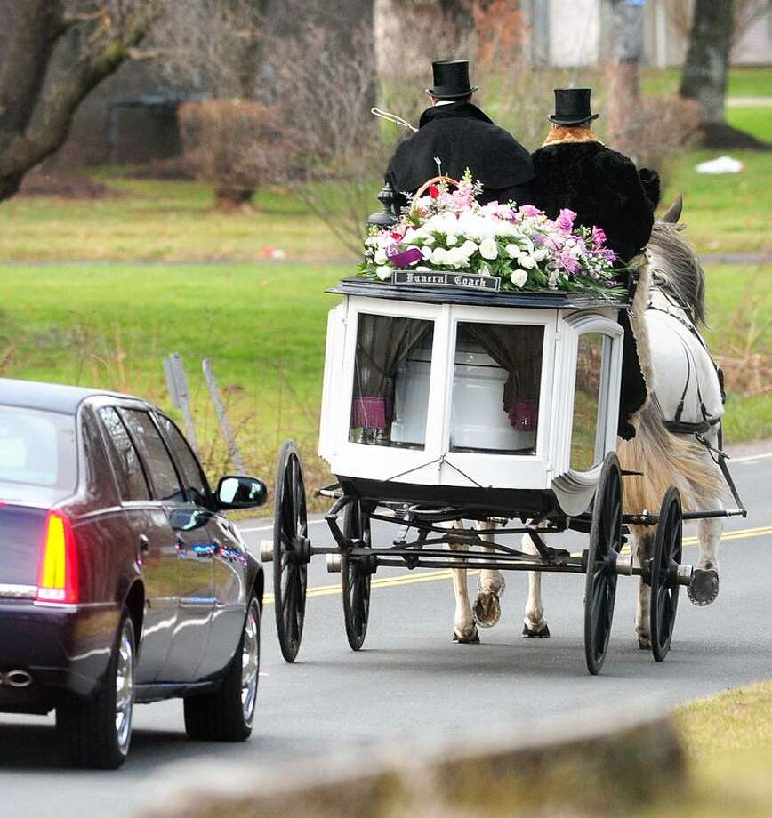 A horse drawn funeral coach carries the body of Sandy Hook Elementary School shooting victim Ana Grace Marquez-Greene from funeral services at The First Cathedral in Bloomfield on 12/22/2012.  On the carriage are Randy Franklin (left) and John Allegra (right) of Allegra Farm.Photo by Arnold Gold/New Haven Register