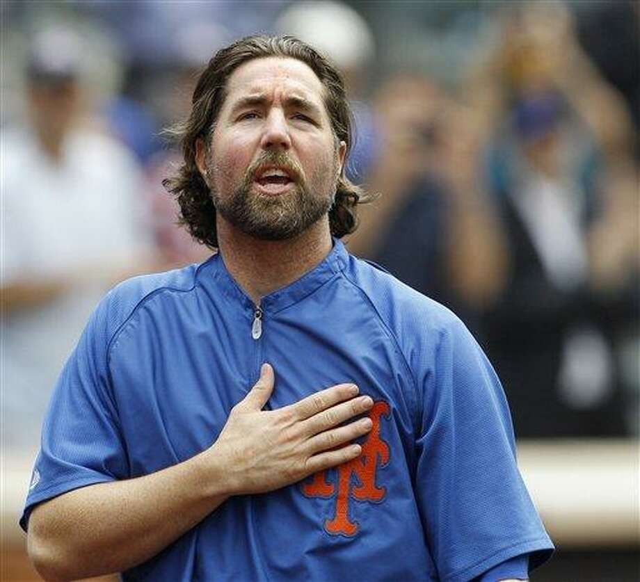 FILE - This Sept. 27, 2012 file photo shows New York Mets starting pitcher R.A. Dickey reacting to fans as he celebrates his 20th victory of the season after the Mets 6-5 win against the Pittsburgh Pirates in a baseball game at Citi Field in New York. A person familiar with the deal tells The Associated Press that Dickey and the Blue Jays have agreed on a new contract, clearing the way for the New York Mets to trade the Cy Young winner to Toronto. The person spoke on condition of anonymity Monday, Dec. 17, 2012,  because the trade was not yet complete. The 38-year-old knuckleballer must pass a physical before he joins the Blue Jays. The Mets would get prized catching prospect Travis d'Arnaud as the centerpiece of the multiplayer swap. (AP Photo/Kathy Willens, File) Photo: ASSOCIATED PRESS / A20122012