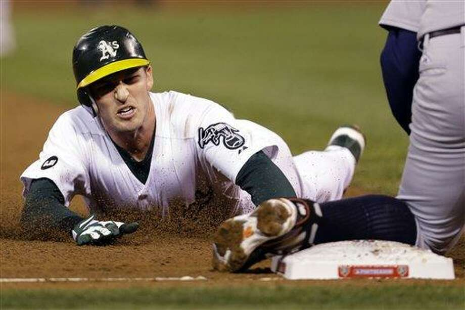 Oakland Athletics' Stephen Drew is out at third on a tag by Detroit Tigers third baseman Miguel Cabrera after hitting an RBI double to score Coco Crisp in the sixth inning of Game 4 of their American League division baseball series in Oakland, Calif., Wednesday, Oct. 10, 2012. (AP Photo/Marcio Jose Sanchez) Photo: ASSOCIATED PRESS / AP2012