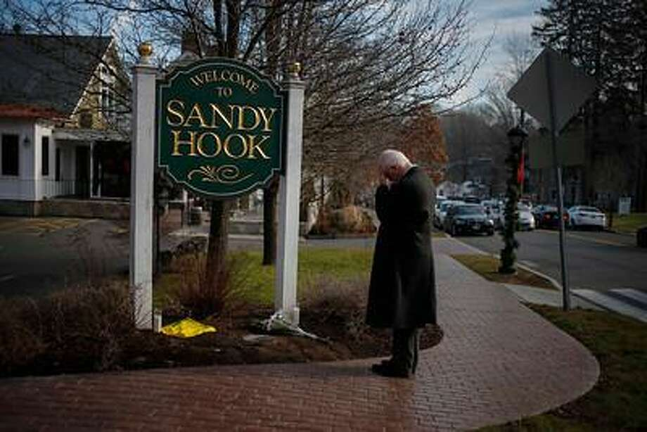 New Jersey resident Steve Wruble, who was moved to drive out to Connecticut to support local residents, grieves for victims of an elementary school mass shooting at the entrance to Sandy Hook village in Newtown, Connecticut December 15, 2012. REUTERS/Adrees Latif