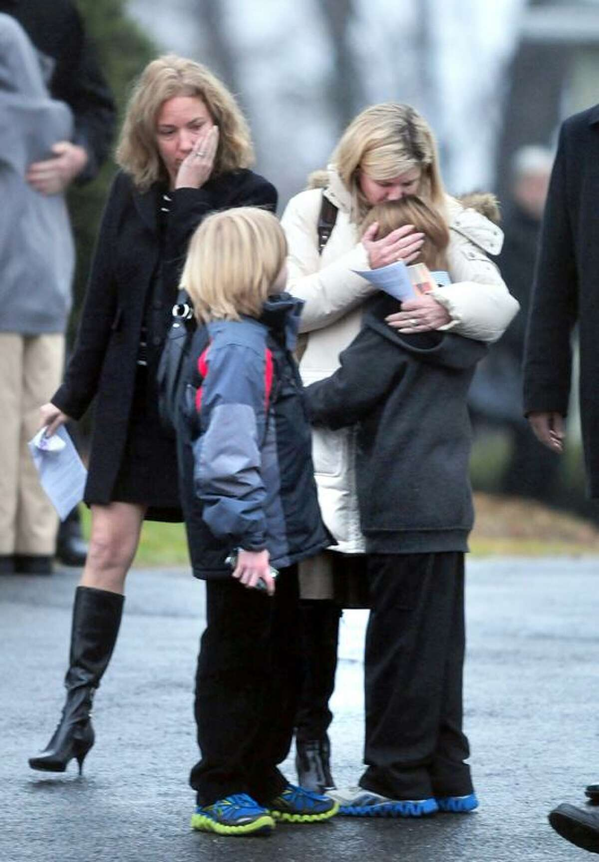Mourners embrace as they leave the Honan Funeral Home in Newtown on 12/17/2012 after funeral services for six-year-old Jack Pinto, a victim of the Sandy Hook Elementary School shootings.Photo by Arnold Gold/New Haven Register