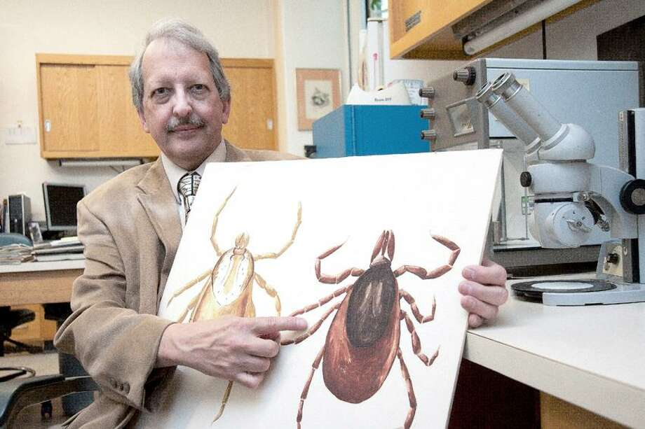 Kirby C. Stafford lll, chief entomologist and tick expert at the Connecticut Agricultural Experiment Station at 24 Hunington Street in New Haven points at a depiction of a mature deer tick (alongside a dog tick), a major perpetrator of Lyme disease, Friday May 25, 2012. vm Williams 05.25.2012