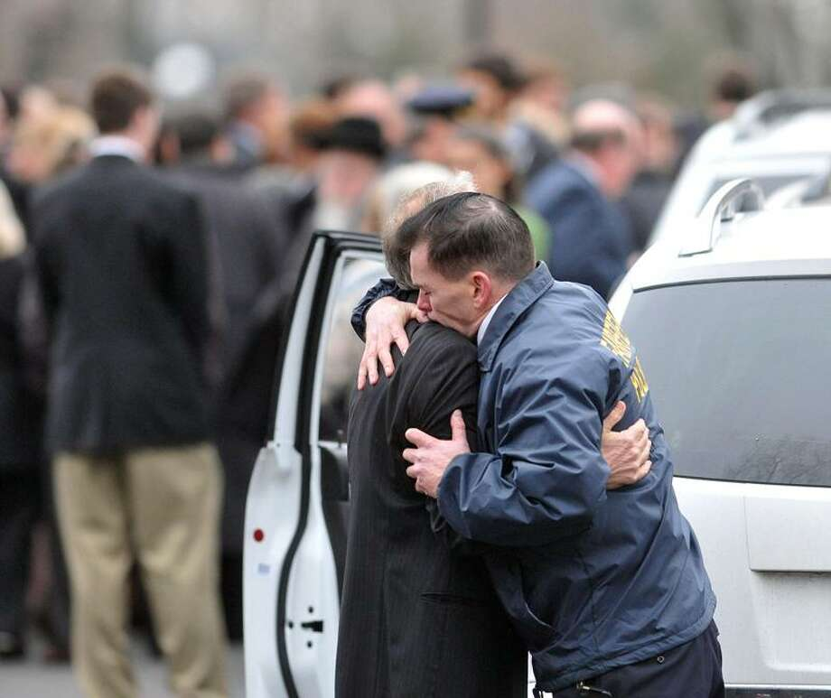 Fairfield Police Chief hugs a family member outside the Abraham L. Green & Son Funeral Home in Fairfield after services for Noah Pozner, 6, victim of the Sandy Hook Elementary School massacre. Peter Casolino/Register