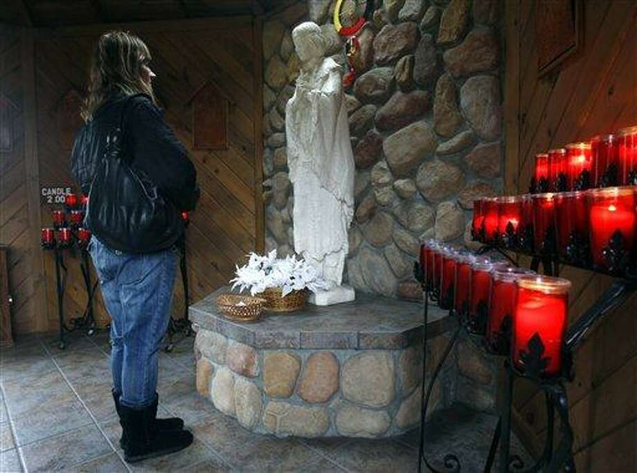 In this Wednesday, Dec. 21, 2011 file photo, Phyllis Tessitore of Amsterdam, N.Y., says a prayer in front of a statue of the the Blessed Kateri Tekakwitha at the National Kateri Shrine and Indian Museum in Fonda, N.Y. On Sunday, Oct. 21, 2012 the Vatican will formally recognize Tekakwitha, a 17th-century Mohawk Indian who spent most of her life in what is now upstate New York, as a saint. (AP Photo/Mike Groll) Photo: ASSOCIATED PRESS / AP2012