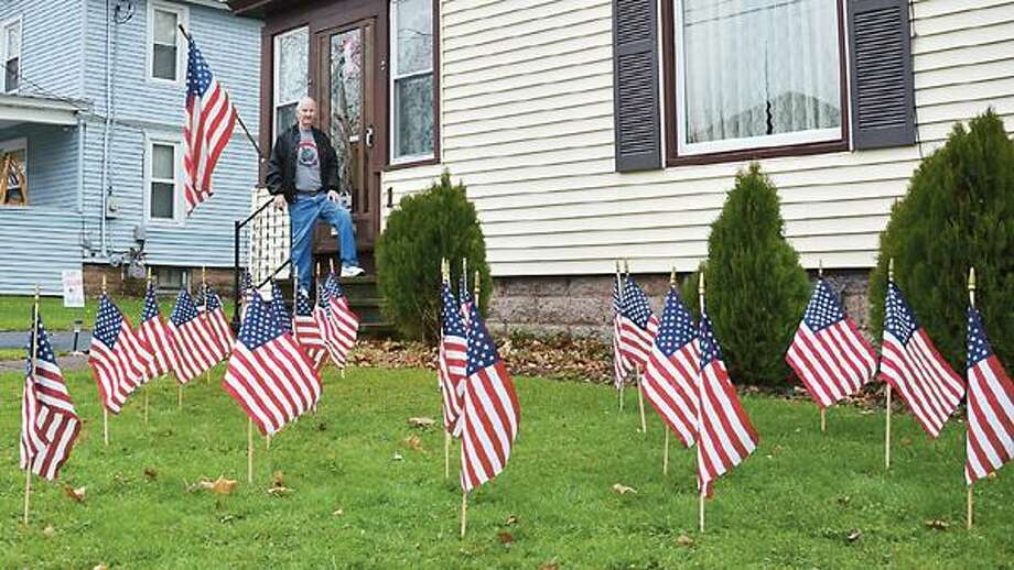 Dispatch Staff Photo by NICK WILL Jack Bernet stands behind the 26 flags in his Sherrill yard. He said he'll put a flag away each time one of the Sandy Hook shooting victims is laid to rest.