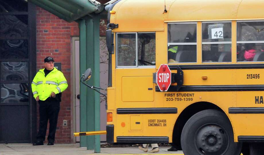 Hamden Police Officer Mike Romanelli was stationed at the door to Dunbar Hill School in Hamden during dismissal. The school had police presence at both arrival and departure of students today. Mara Lavitt/New Haven Register12/17/12