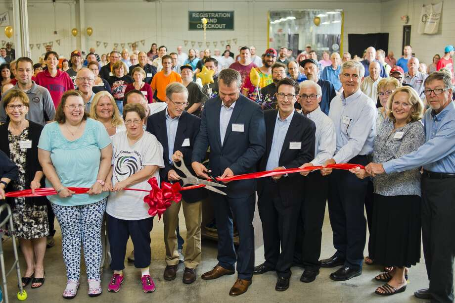 Arnold Center Vice President Chris Chamberlain, center left, and Board Chair Tom Kreucher, center right, cut a ceremonial ribbon alongside other board members, city officials, and Arnold Center staff and participants during a 50th anniversary celebration on Wednesday, July 26, 2017. Photo: (Katy Kildee/kkildee@mdn.net)