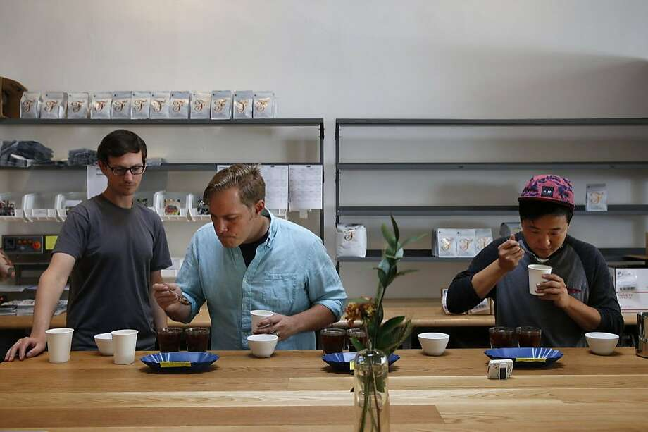Owner Kevin Bohlin, center, tastes coffee samples with John Felder, left, and Joshua Lee at Saint Frank Coffee's roastery on Mission Street in San Francisco. Photo: Leah Millis, The Chronicle