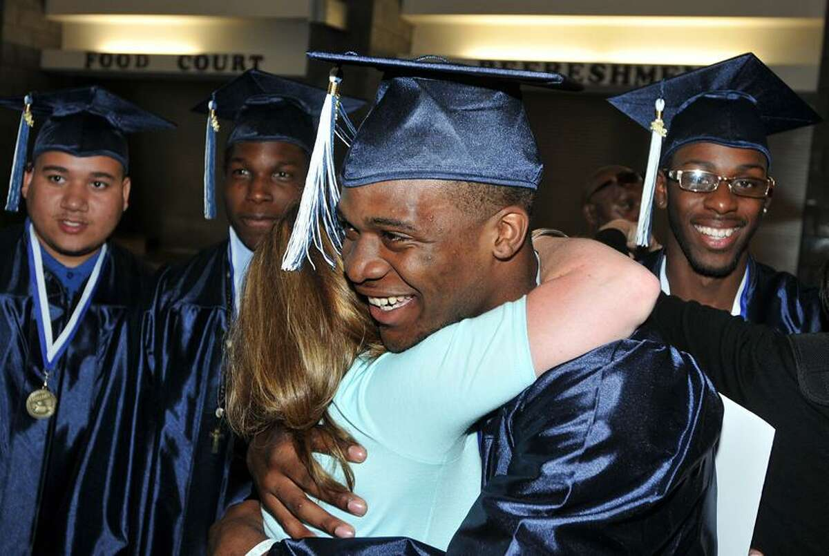 Hillhouse graduate Daishawn Crudup gets a hug from former assistant principal, Nadine Gannon, as students prepared for the Hillhouse High graduation. Peter Casolino/New Haven Register