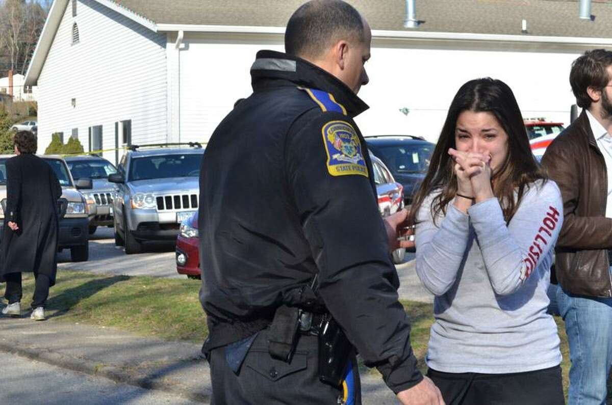 An unidentified woman asks a police officer for information about a teacher after a shooting spree threw Sandy Hook Elementary School in Newtown into turmoil Friday morning. Melanie Stengel/Register