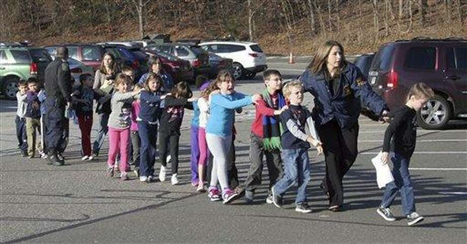 In this photo provided by the Newtown Bee, State Police lead children from the Sandy Hook Elementary School in Newtown following a reported shooting there Friday. (AP Photo/Newtown Bee, Shannon Hicks) Photo: AP / Newtown Bee