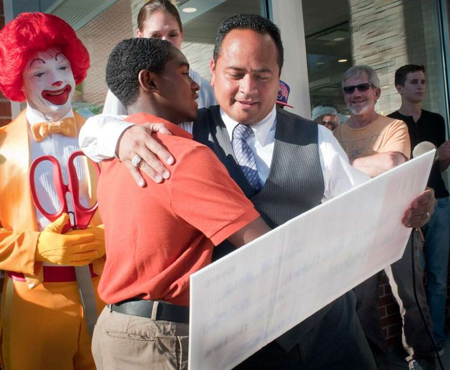 Trevonn Cohen, left, is presented with a scholarship check for $750 by Joe Rodriguez during grand re-opening ceremonies at the McDonald's at 1094 Whalley Ave. Rodriguez owns several McDonald's in the area.    Melanie Stengel/Register