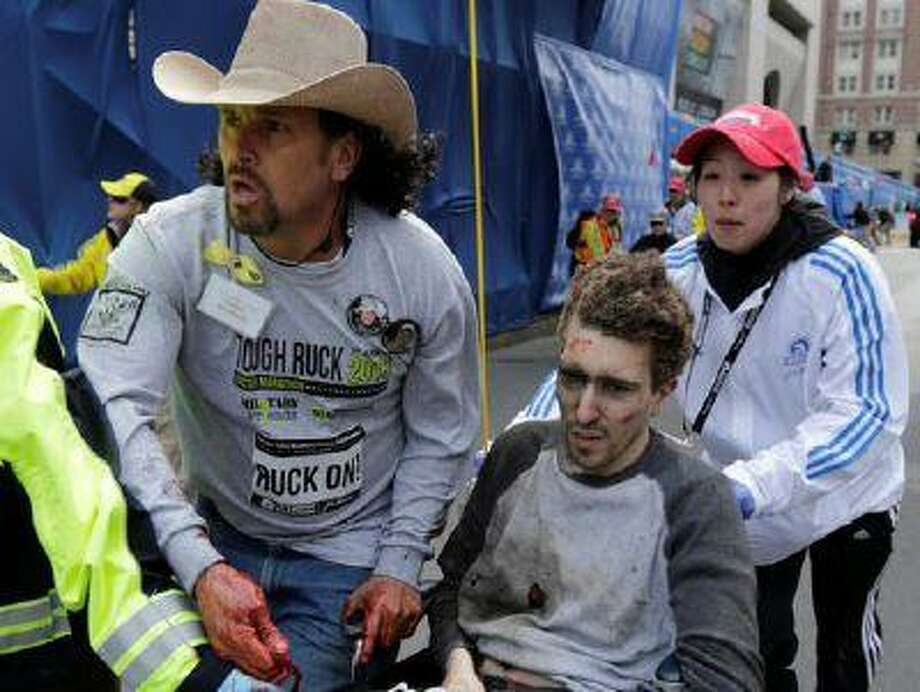An emergency responder and two volunteers, including Carlos Arredondo, center, push Jeff Bauman in a wheel chair after he was injured in an explosion near the finish line of the Boston Marathon, Monday, April 15, 2013 in Boston. At least three people were killed, including an 8-year-old boy, and more than 170 were wounded when two bombs blew up seconds apart. (AP Photo/Charles Krupa, File)