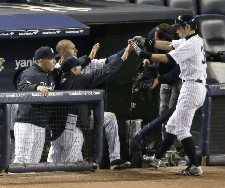 New York Yankees' Ichiro Suzuki is congratulated by teammates after hitting a two-run home run in the ninth inning during Game 1 of the American League championship series Saturday, Oct. 13, 2012, in New York. (AP Photo/Charlie Riedel) Photo: AP / AP2012